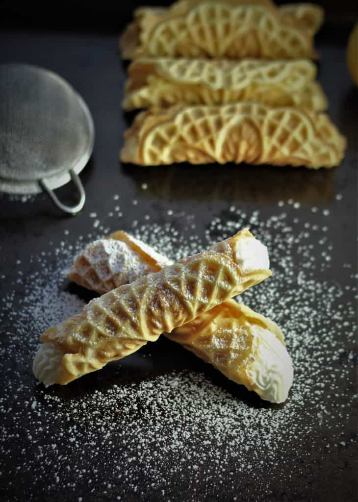 two ricotta filled pizzelle with pizzelle shells in background