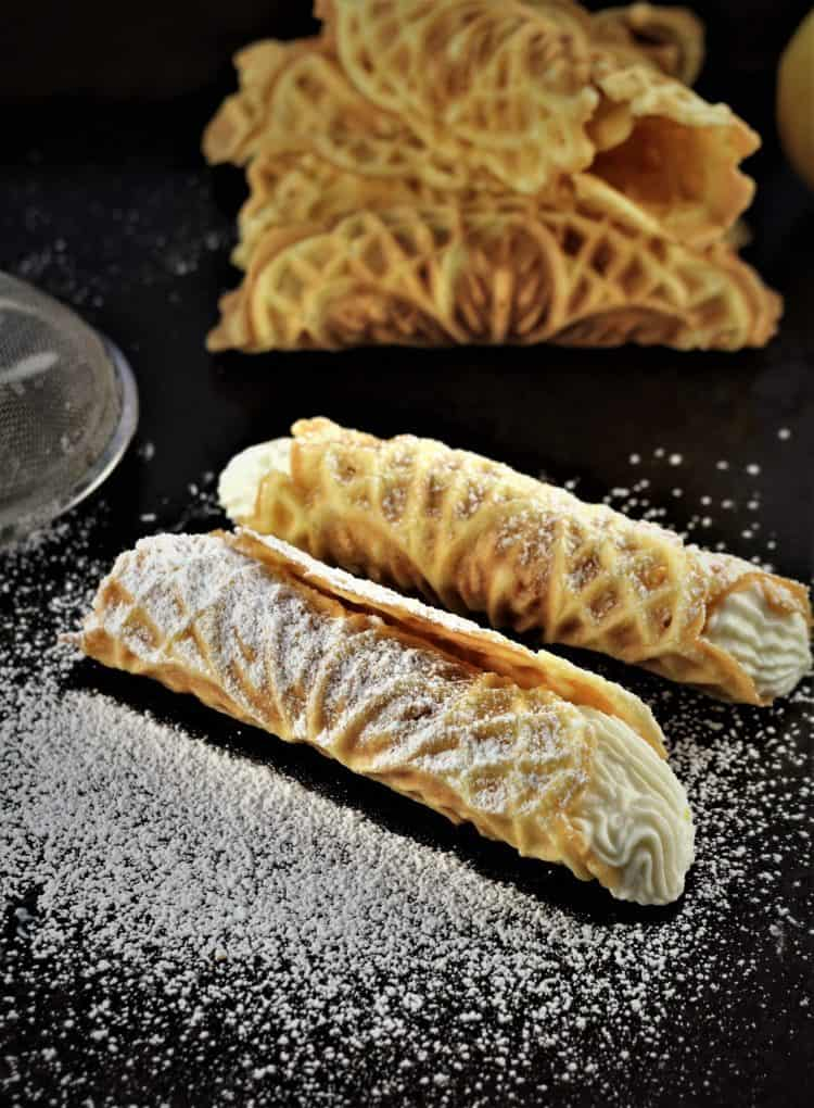 two pizzelle filled with ricotta and dusted with powdered sugar
