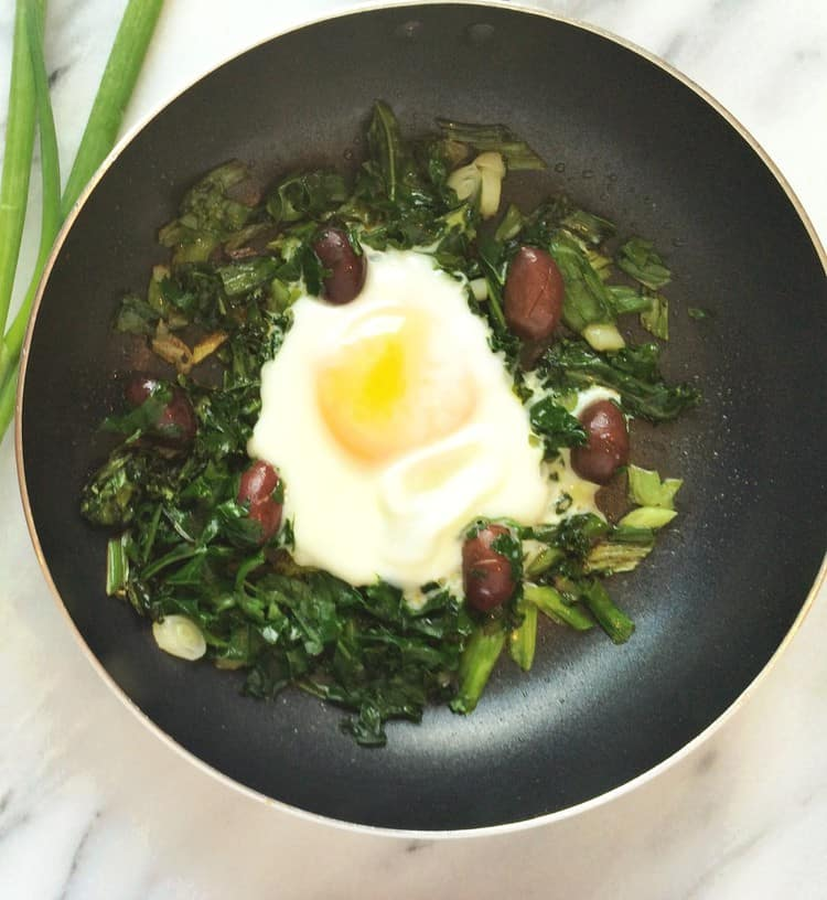 pan with sunny side up egg surrounded by greens