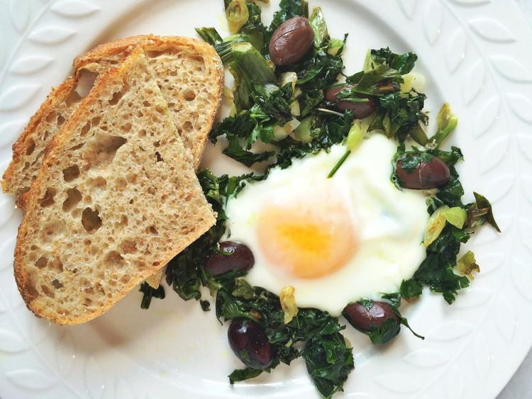 plate with fried egg with greens with slices of bread