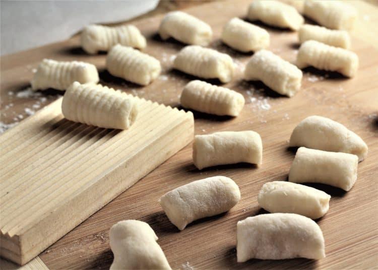 rolling gnocchi on a wooden gnocchi board