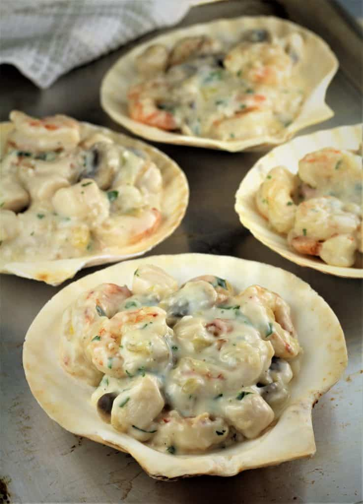 scallop shells filled with seafood and bechamel sauce mixture