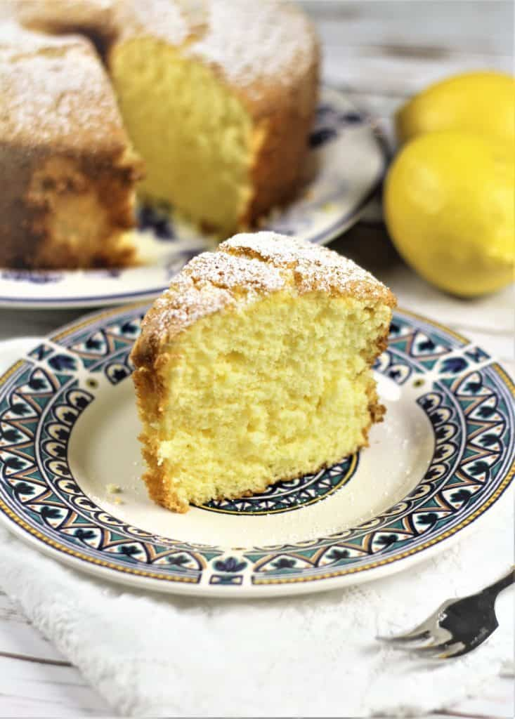 slice of Nonna's Sponge Cake with full cake in background and lemon on the side