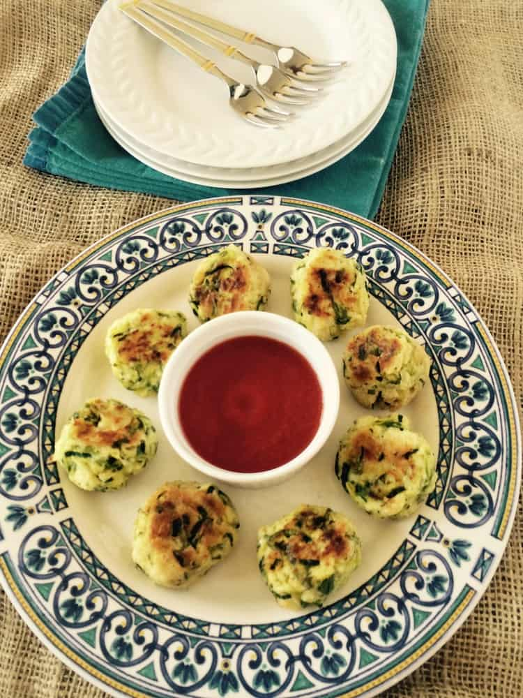 plate with spiralized zucchini ricotta meatballs around a bowl of marinara sauce