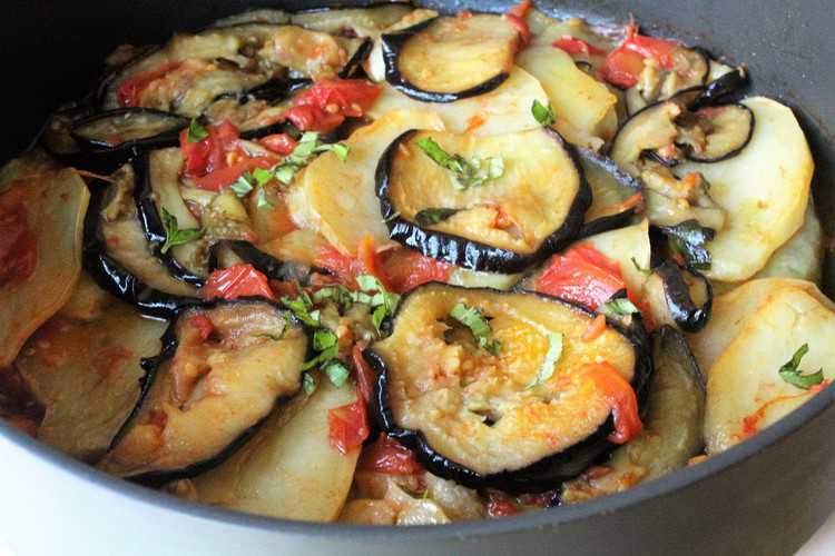 pan with sliced baked eggplant, potatoes, and tomato sauce