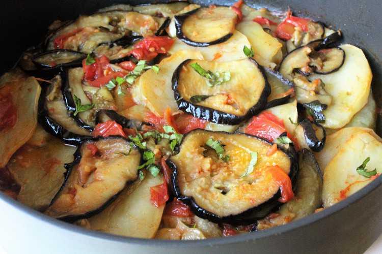 pan with sliced baked eggplant, potatoes, and tomato sauce