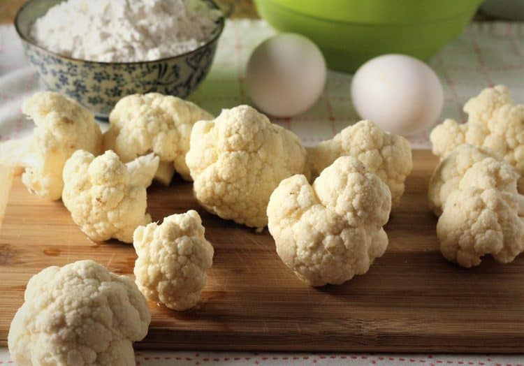 cauliflower florets on cutting board with eggs and flour in background
