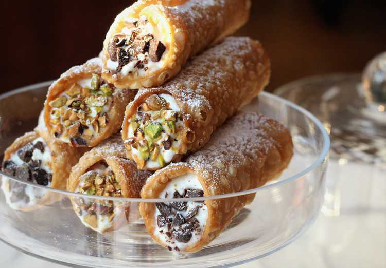 glass plate piled with sicilian cannoli