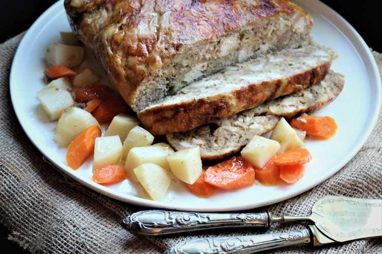 sliced stuffed chicken on white round platter with carrots and potatoes