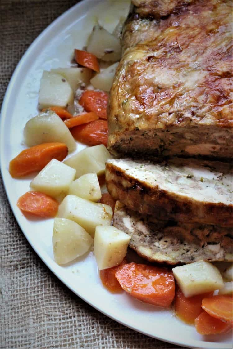 sliced stuffed chicken on platter surrounded by carrots and potatoes