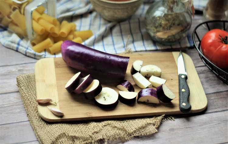 eggplant cut into cubes on cutting board with knife on side and jar of pasta behind