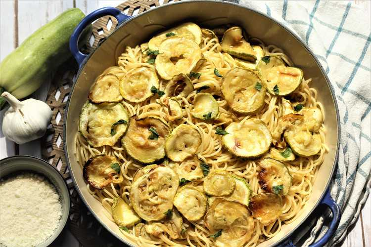 large skillet filled with spaghetti and zucchini surrounded by zucchini, garlic bulb and bowl of cheese