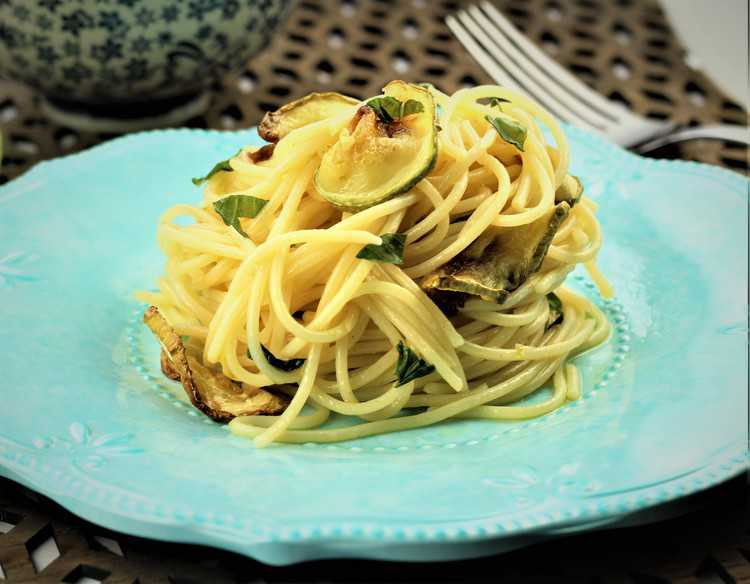 blue plate with spaghetti with zucchini slices and fork on side