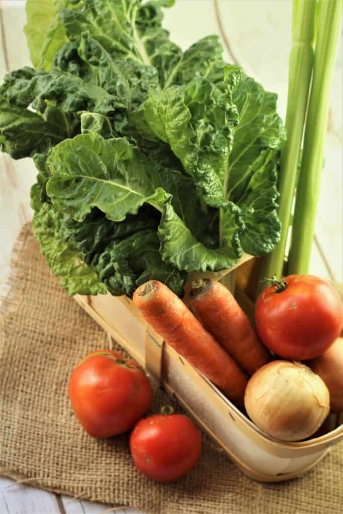 basket with swiss chard, carrots, tomatoes and onion