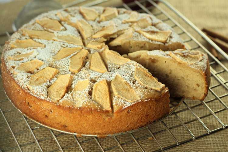 apple yogurt cake on wire rack with wedge cut from it