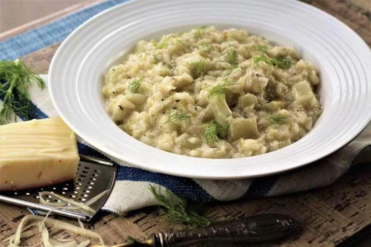 bowl of fennel and leek risotto with a cheese grater and piece of cheese