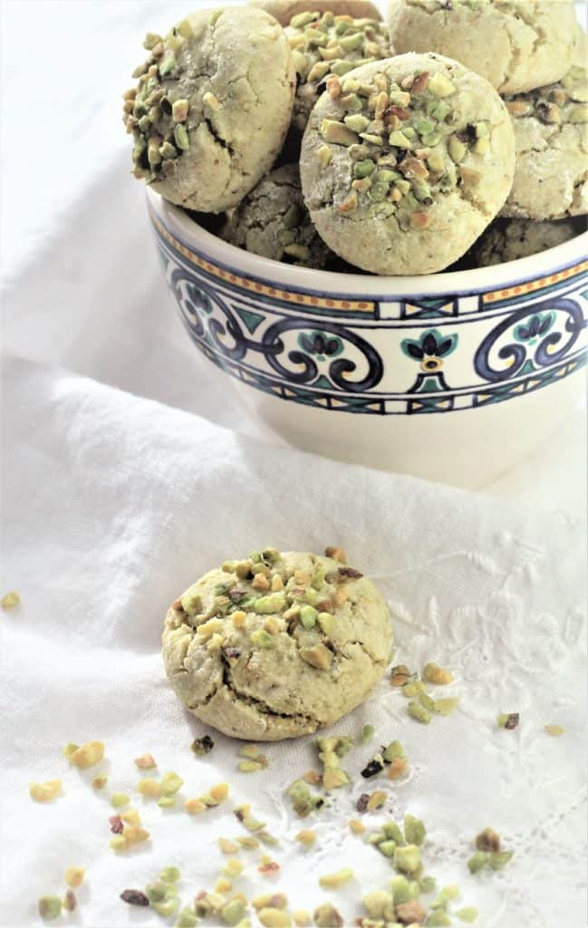 coffee cup filled with pistachio amaretti cookies with one cookie resting on the table cloth next to it
