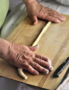 rope of sweet taralli dough being rolled on a wooden board