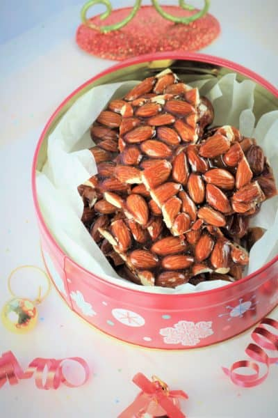 pieces of Sicilian Almond Torrone presented in a Christmas tin