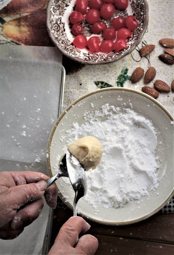 ball of Italian orange juice cookie being scraped into a bowl of powdered sugar