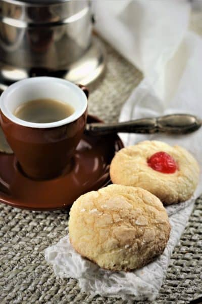 two cookies next to a cup of espresso with coffee maker in background