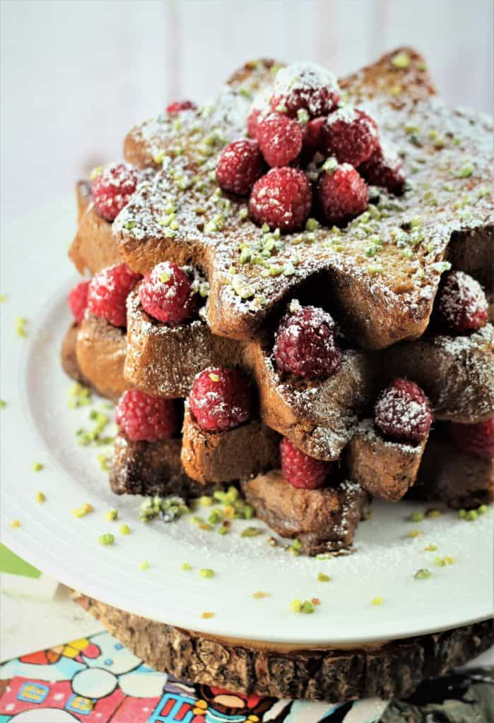 presentation of Pandoro french toast with raspberries, pistachios and powdered sugar