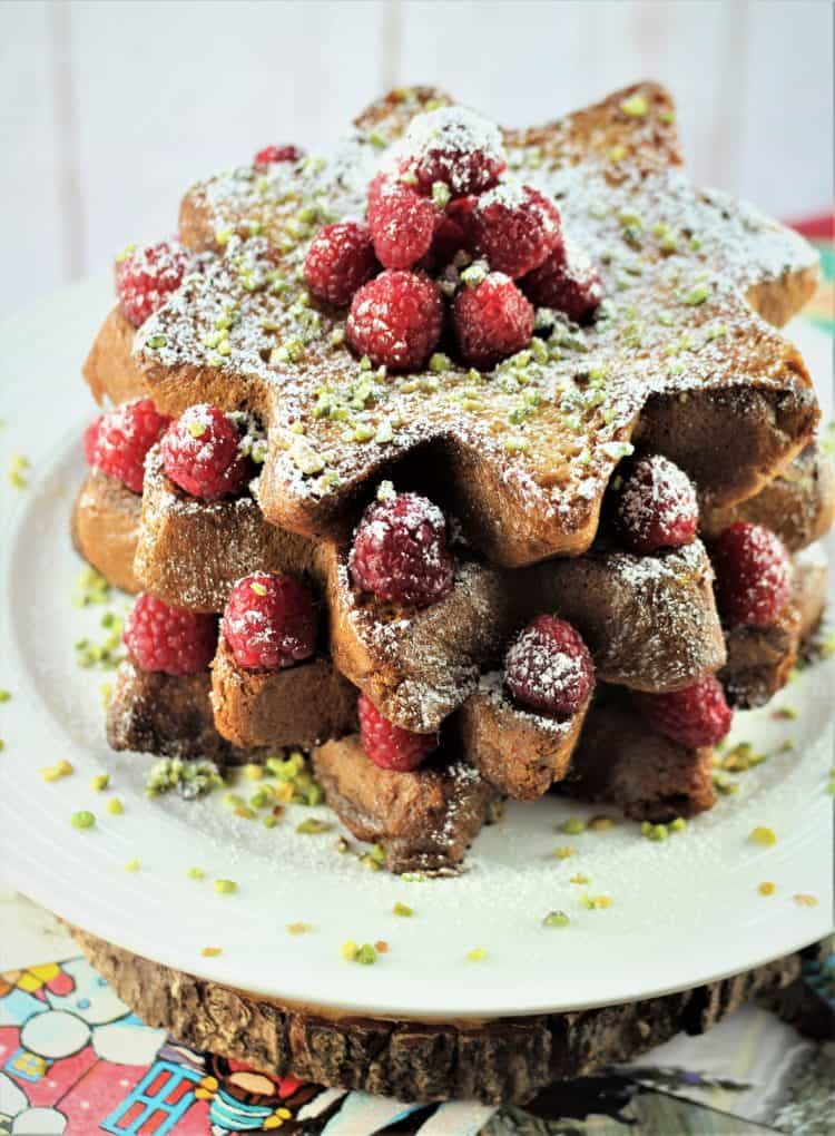 Pandoro french toast slices topped with raspberries, pistachios and powdered sugar