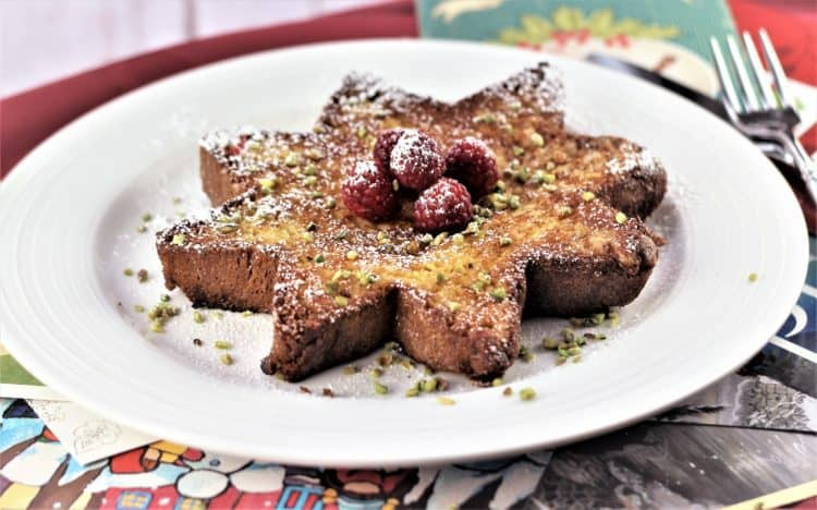 slice of star shaped Pandoro french toast topped with raspberries and pistachios