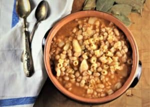 White Bean and Potato Soup seen overhead served in a ceramic dish with spoons at the side