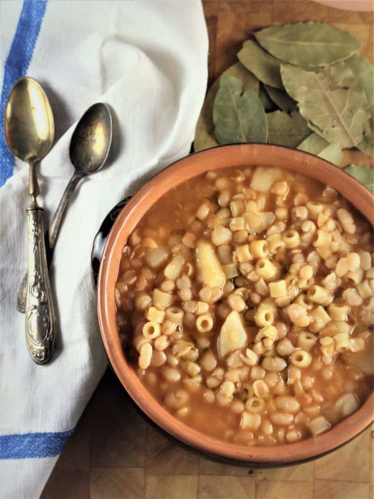 White Bean and Potato Soup served in ceramic dish with spoons on the side and bay leaves scattered in background