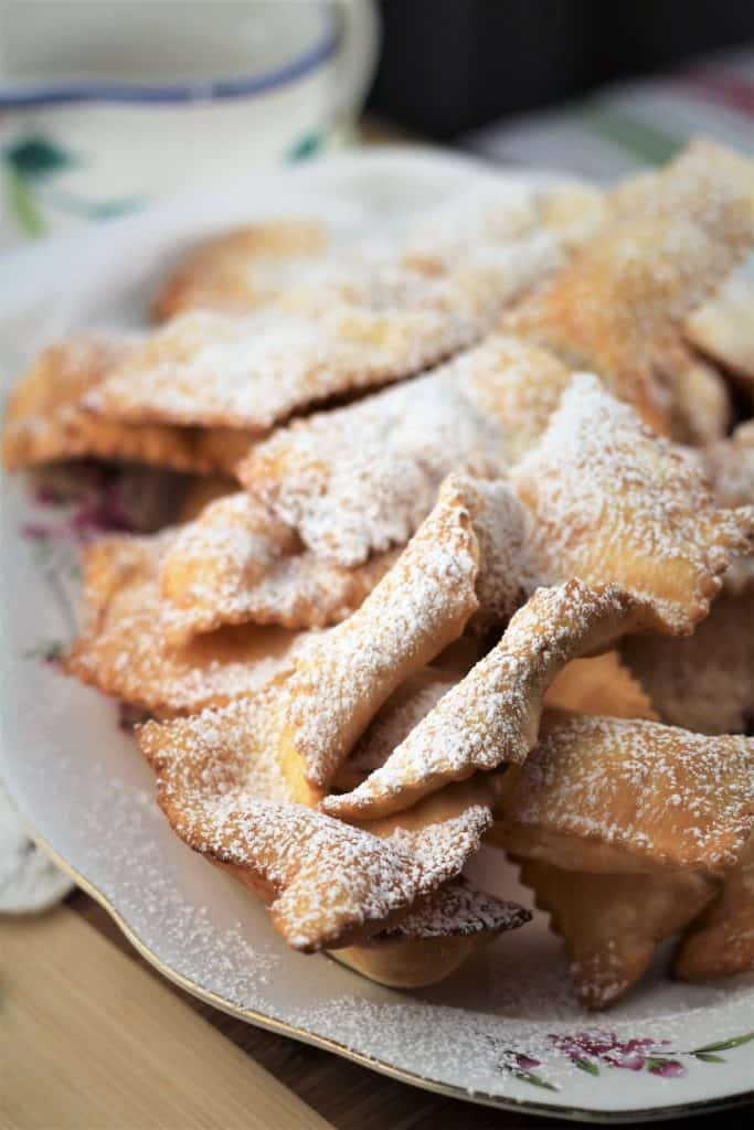 Chiacchiere di Carnevale dusted in powdered sugar on a platter