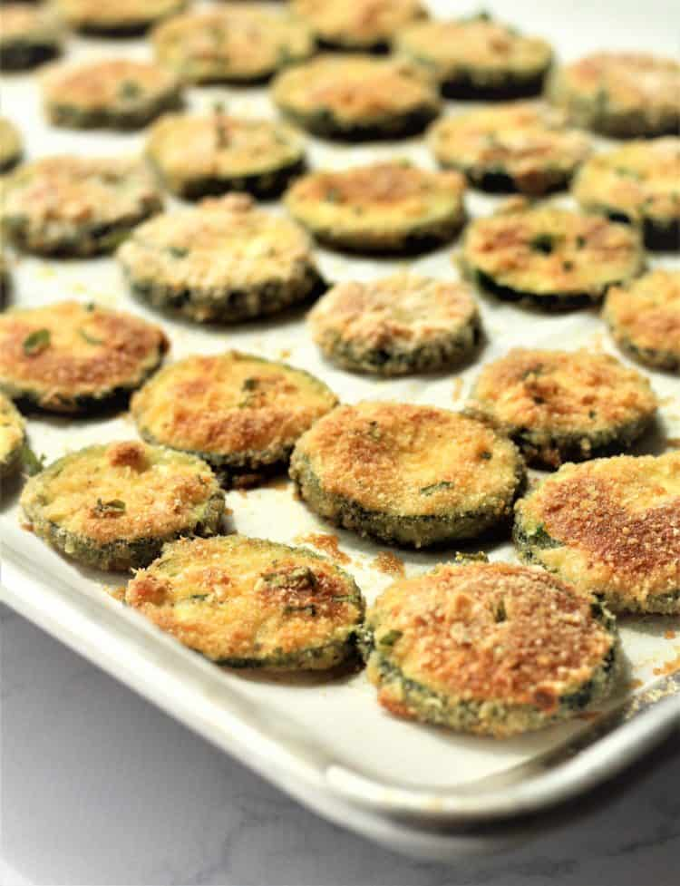 zucchini crisps shown on baking sheet right out of the oven