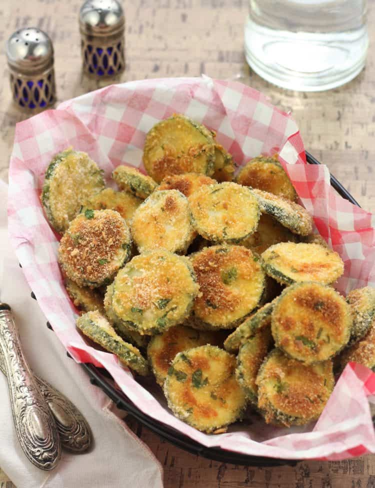 Baked Parmesan Zucchini Crisps served in a basket with utensils on side