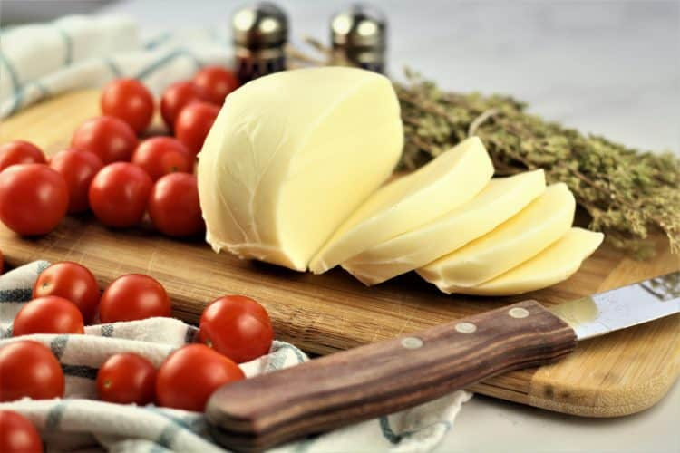 slices of mozzarella on cutting board with cherry tomatoes and oregano