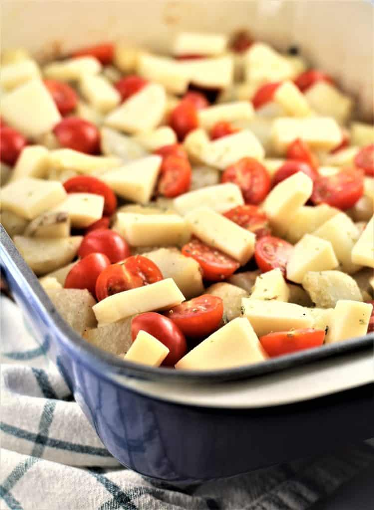 baking pan with roast potatoes topped with mozzarella cubes and cherry tomatoes