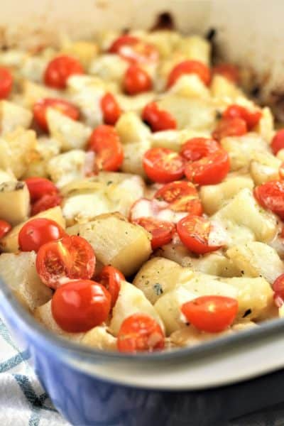 roast potatoes with mozzarella and cherry tomatoes in a blue baking dish
