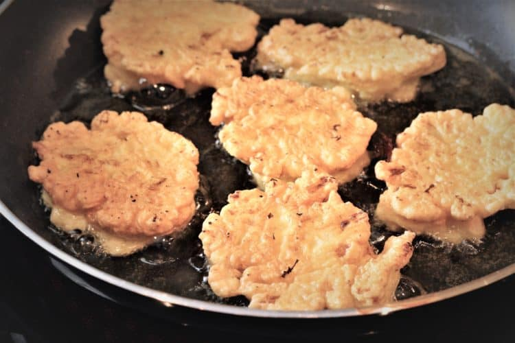 cauliflower fritters frying in skillet