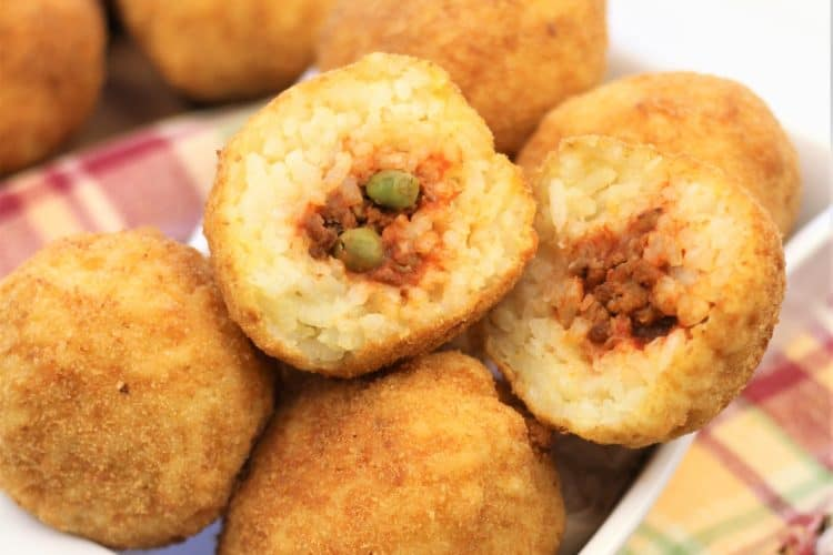 arancini in a plate with one shown cut open