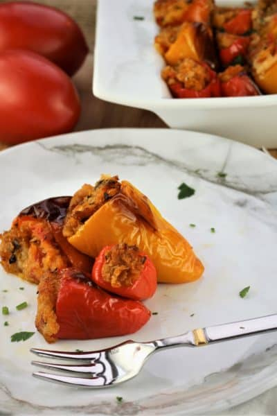 stuffed mini peppers on a white plate with fork