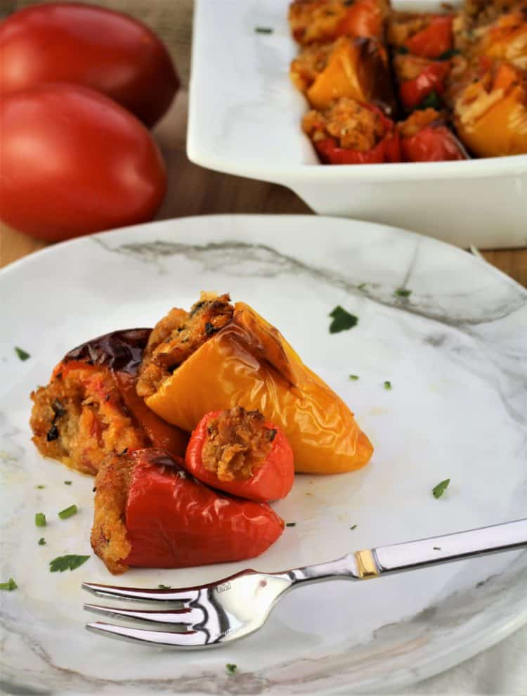 white plate with 4 mini stuffed peppers and fork