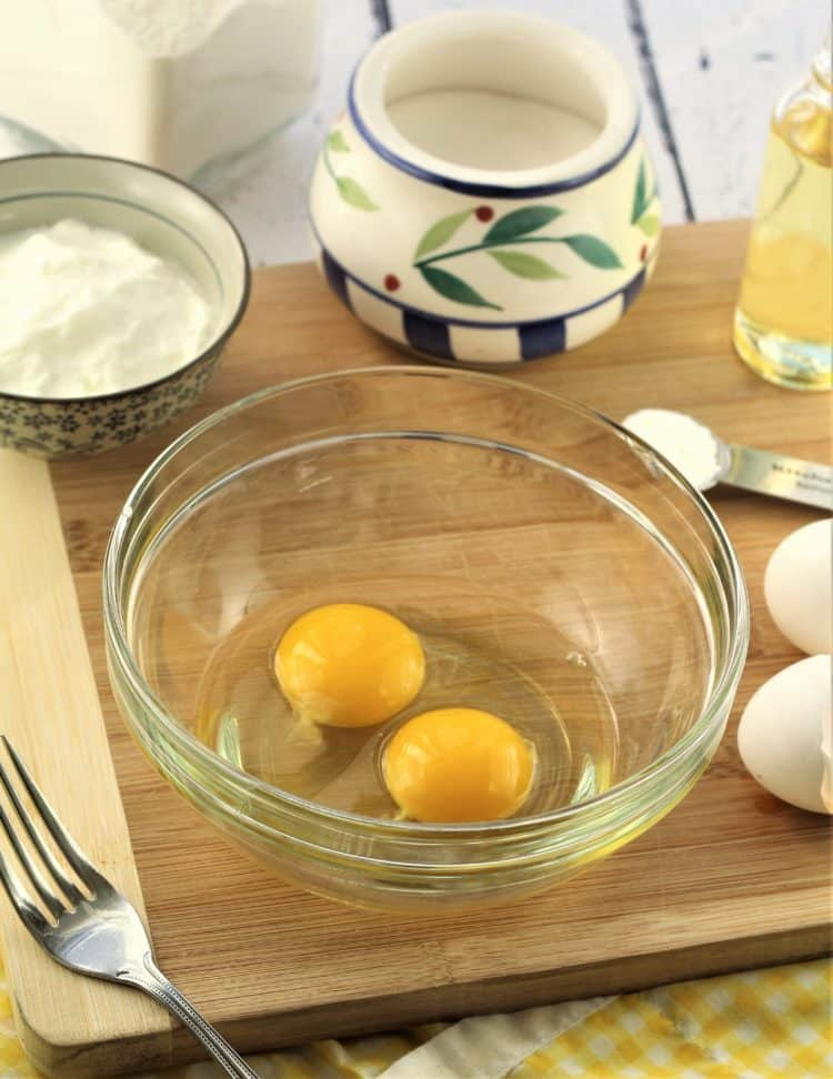 glass bowl with eggs, yogurt, flour and sugar in background