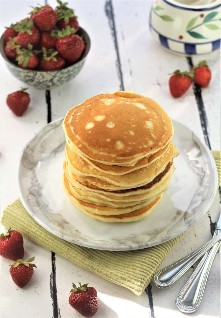 stack of pancakes with bowl of strawberries and sugar bowl in background