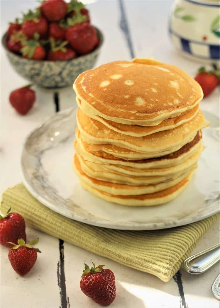 stack of pancakes with bowl of strawberries in background