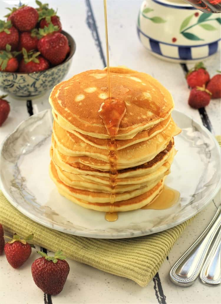 stack of yogurt pancakes with maple syrup drizzled on top and bowl of strawberries in background