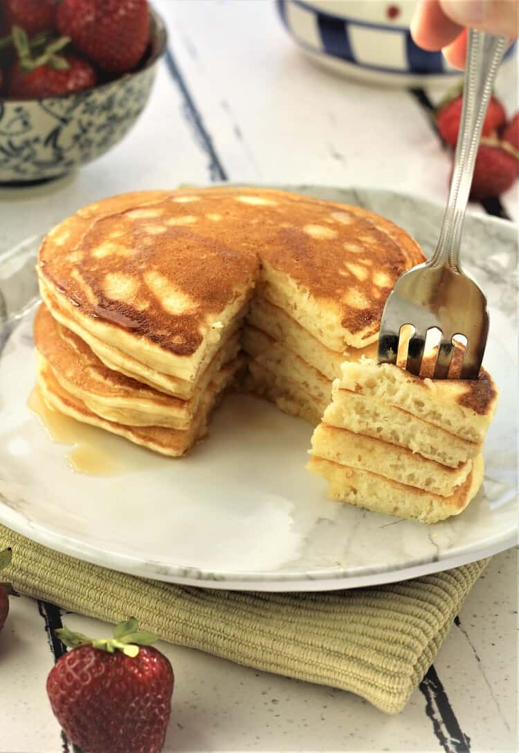 stack of pancakes with fork wedged in a bite