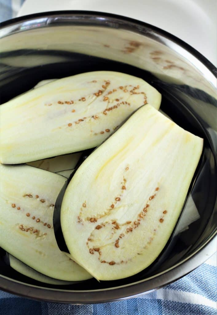 sliced eggplants submerged in a bowl of water