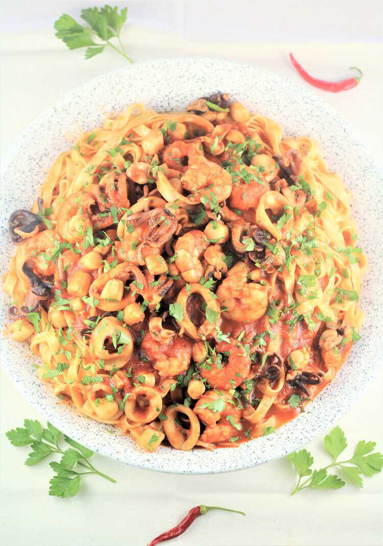 bowl of egg pasta topped with seafood and chopped parsley