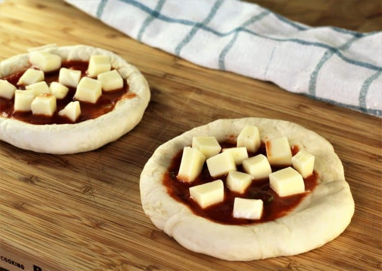 two unbaked mini pizzas with tomato sauce and cubed mozzarella on wooden board