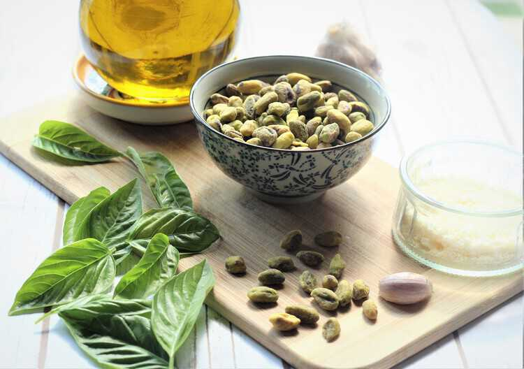 bowl of pistachios, basil leaves, parmigiano cheese, garlic and jar of olive oil