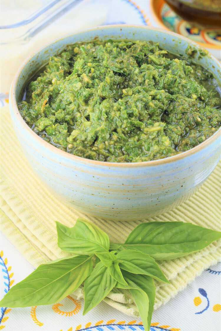 bowl filled with basil pesto and fresh basil leaves on the side